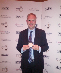 Jeremy Watkin holding Phone.com's bronze Stevie Award for Customer Service Department of the Year